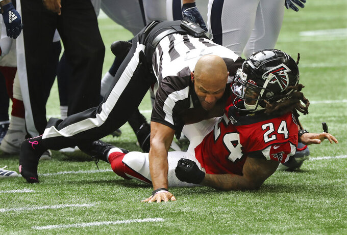 Referee Terry McAulay, left, breaks up an altercation between Atlanta Falcons running back Devonta Freeman (24) and Los Angeles Rams defensive tackle Aaron Donald during the second half of an NFL football game, Sunday, Oct. 20, 2019, in Atlanta. (Curtis Compton/Atlanta Journal Constitution via AP)