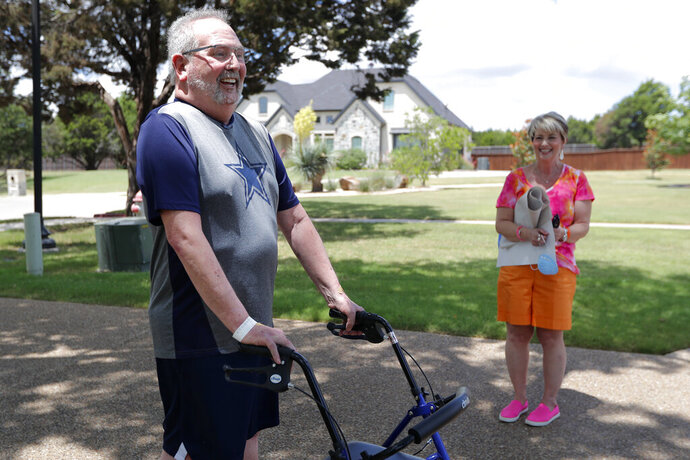 Stephen Donelson, left, smiles as he walks up his driveway to his home accompanied by his wife, Terri, in Midlothian, Texas on Friday, June 19, 2020, after his 90-day stay in the Zale Hospital on the UT Southwestern Campus. Donelson's family hadn't left the house in two weeks after COVID-19 started spreading in Texas, hoping to shield the organ transplant recipient. Yet one night, his wife found him barely breathing, his skin turning blue, and called 911. (AP Photo/Tony Gutierrez)
