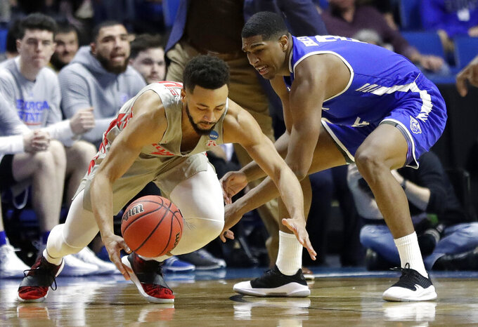 Houston's Galen Robinson Jr., left, and Georgia State's Malik Benlevi dive after a loose ball during the first half of a first round men's college basketball game in the NCAA Tournament Friday, March 22, 2019, in Tulsa, Okla. (AP Photo/Jeff Roberson)