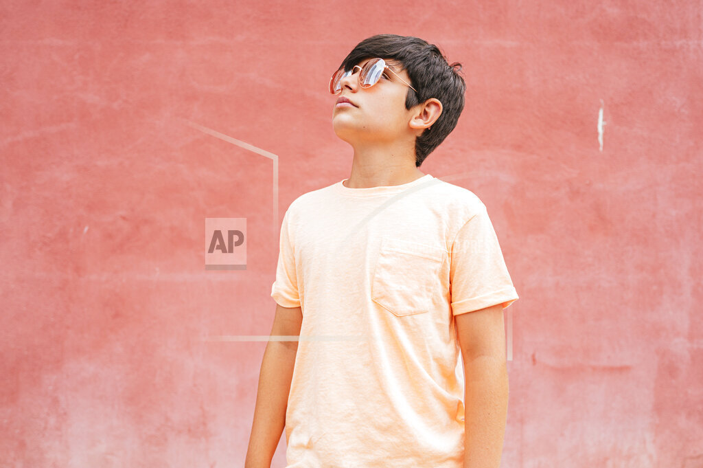 Thoughtful boy wearing sunglasses standing in front of red wall