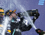 Race winner, Mercedes driver Valtteri Bottas of Finland, centre, drinks champagne by second placed Red Bull driver Max Verstappen of the Netherlands, left, after the Russian Formula One Grand Prix, at the Sochi Autodrom circuit, in Sochi, Russia, Sunday, Sept. 27, 2020. (Yuri Kochetkov, Pool Photo via AP)