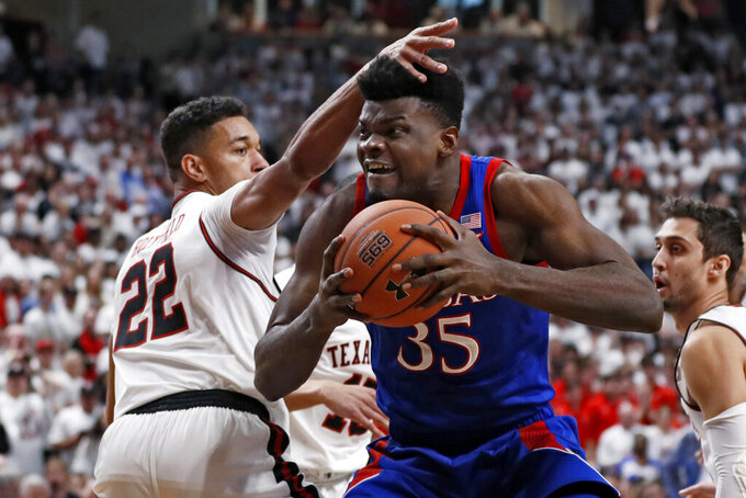 Texas Tech's TJ Holyfield (22) defends against Kansas' Udoka Azubuike (35) during the first half of an NCAA college basketball game Saturday, March 7, 2020, in Lubbock, Texas. (AP Photo/Brad Tollefson)