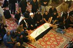 FILE - In this Saturday, Oct. 5, 2019 file photo, mourners pray over the flag-draped coffin of a protester killed during anti-government protesters during his funeral at the Imam Ali shrine in Najaf, Iraq. The protests have plunged the country into a new cycle of instability since last week, one that could potentially be the most dangerous this conflict-scarred nation has had to face, with more than 100 killed in less than a week. Iraqi security forces have been shooting at young Iraqis demanding jobs, electricity and clean water and an end to corruption. (AP Photo/Anmar Khalil, File)