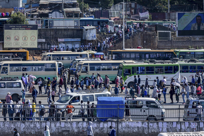 Passengers queue to get on buses in the capital Addis Ababa, Ethiopia Friday, Nov. 6, 2020. Ethiopia's prime minister says airstrikes have been carried out against the forces of the country's Tigray region, asserting that the strikes in multiple locations