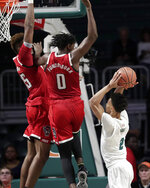 Miami guard Isaiah Wong, right, shoots as North Carolina State forward Manny Bates (15) and forward DJ Funderburk (0) defend during the first half of an NCAA college basketball game, Wednesday, Feb. 5, 2020, in Coral Gables, Fla. (AP Photo/Lynne Sladky)