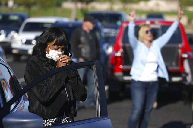 FILE - In this April 12, 2020, file photo, keeping to safe social distance guidelines, worshipers pray at their own vehicles as they attend an outside drive-in Easter service at the Living Word church due to the coronavirus in Mesa, Ariz. What began as a single case of a new coronavirus infecting a person affiliated with Arizona State University on Jan. 26 turned into a vast outbreak afflicting hundreds of thousands of Arizonans that had killed nearly 8,000 by the end of the year. The coronavirus pandemic was Arizona's top news story of the year. (AP Photo/Ross D. Franklin, File)