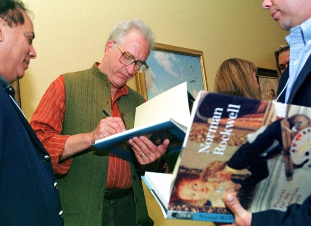 FILE - In this June 7, 2001 file photo, Peter Rockwell autographs a book  at The Rockwell Museum in Stockbridge, Mass.  Rockwell, whose famous father's iconic images graced the covers of the Saturday Evening Post and who became a noted artist in his own right, has died. He was 83. The third and youngest son of Norman Rockwell died Feb. 6, 2020 in Danvers, Mass., where he spent the last few weeks of his life enjoying visits by his family, according to the Norman Rockwell Museum in Stockbridge.. (AP Photo/Nancy Palmieri, File)