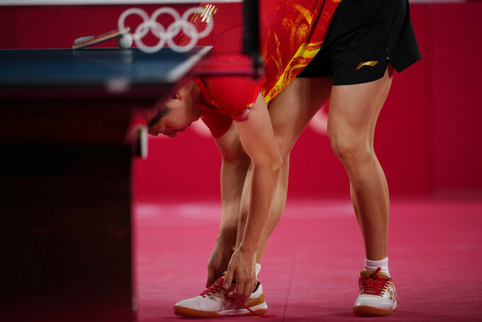 China's Ma Long ties his shoes during the table tennis men's singles quarterfinal match against Egypt's Omar Assarat at the 2020 Summer Olympics, Wednesday, July 28, 2021, in Tokyo. (AP Photo/Kin Cheung)