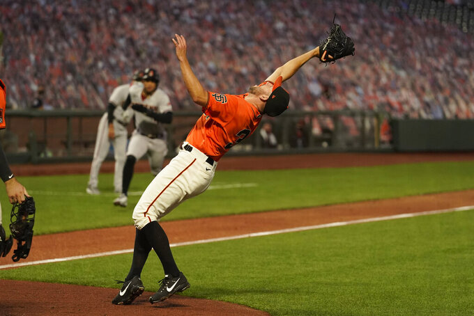 San Francisco Giants starting pitcher Tyler Anderson reaches back to catch a popup by Arizona Diamondbacks' Kole Calhoun in the third inning of a baseball game Friday, Sept. 4, 2020, in San Francisco. (AP Photo/Eric Risberg)