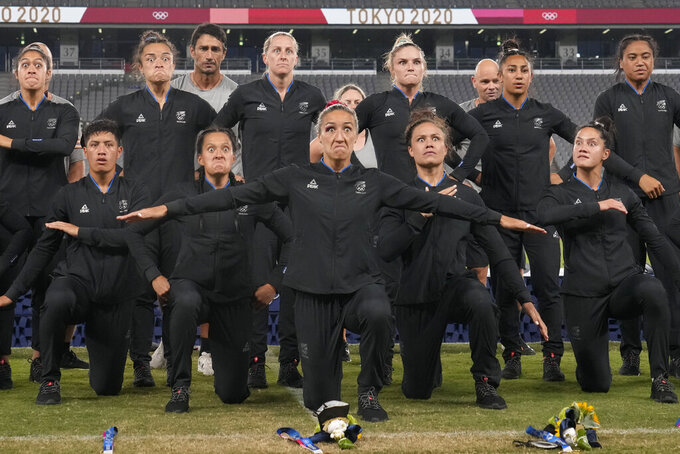 New Zealand players and team staff perform the haka after winning gold in women's rugby sevens at the 2020 Summer Olympics, Saturday, July 31, 2021 in Tokyo, Japan. (AP Photo/Shuji Kajiyama)