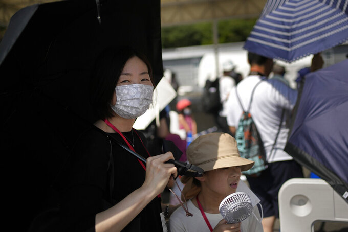 Visitors use umbrellas and fans to beat the heat outside the Fuji International Speedway, the finish for the women's cycling road race that is underway, at the 2020 Summer Olympics, Sunday, July 25, 2021, in Oyama, Japan. (AP Photo/Christophe Ena)