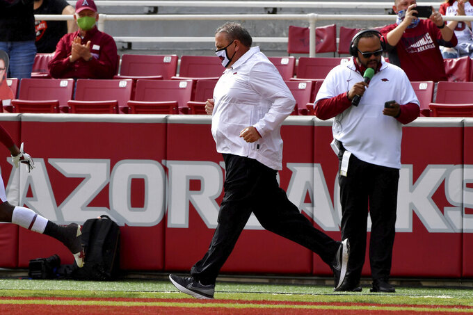 Arkansas coach Sam Pittman, center, heads onto the field before an NCAA college football game against Mississippi, Saturday, Oct. 17, 2020, in Fayetteville, Ark. (AP Photo/Michael Woods)
