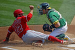 Los Angeles Angels' David Fletcher (22) scores past Oakland Athletics catcher Austin Allen in the first inning of a baseball game Saturday, Aug. 22, 2020, in Oakland, Calif. Fletcher scored on a single by Angels' Mike Trout. (AP Photo/Ben Margot)