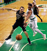 Boston Celtics forward Guerschon Yabusele, right, knocks the ball away from Milwaukee Bucks center Tyler Zeller, left, as they battle for a rebound during the first quarter of Game 2 of an NBA basketball first-round playoff series in Boston, Tuesday, April 17, 2018. (AP Photo/Charles Krupa)