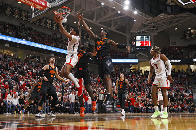 Texas Tech's Kyler Edwards (0) lays the ball up around Oklahoma State's Isaac Likekele (13) and Cameron McGriff (12) during the first half of an NCAA college basketball game Saturday, Jan. 4, 2020, in Lubbock, Texas. (AP Photo/Brad Tollefson)