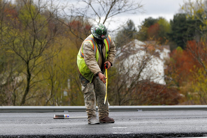 A worker measures along a new stretch of asphalt as paving and construction resume on Interstate 79, Friday, May 1, 2020, in Cranberry Township, Pa. Work at the site halted in mid-March when the state ordered a stop to non-essential business to slow the spread of the new coronavirus. (AP Photo/Keith Srakocic)
