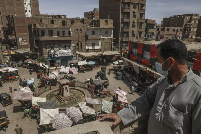 Ashraf Sayed a resident of the town of Monshah, where a surge in coronavirus pandemic cases is taking place, looks at a market on the top of a residential building, in Sohag, Egypt on May 2, 2021. In Sohag province, health workers have grown desperate. One doctor who chairs a major hospital there said the real number of infections is likely 10 times higher than the Health Ministry rate of 400-450 new cases a week. (AP Photo/Mohamed El-Shahed)