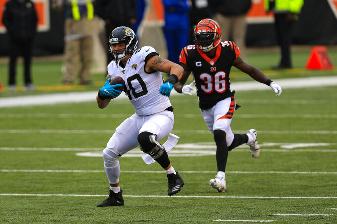 Jacksonville Jaguars tight end James O'Shaughnessy (80) runs after a catch in front of Cincinnati Bengals strong safety Shawn Williams (36) in the second half of an NFL football game in Cincinnati, Sunday, Oct. 4, 2020. (AP Photo/Aaron Doster)
