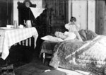 FILE - In this November 1918 photo made available by the Library of Congress, a girl stands next to her sister lying in bed. The girl became so worried she telephoned the Red Cross Home Service who came to help the woman fight the influenza virus. (Library of Congress via AP, File)