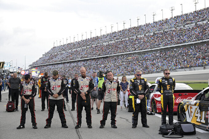 Crew members and drivers stand on pit road before a NASCAR Cup Series auto race at Daytona International Speedway, Saturday, Aug. 28, 2021, in Daytona Beach, Fla. (AP Photo/Phelan M. Ebenhack)