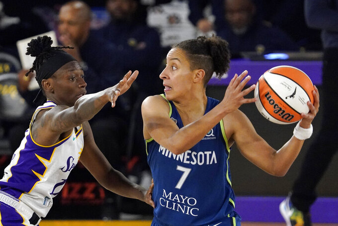 Minnesota Lynx guard Layshia Clarendon, right, tries to pass while under pressure from Los Angeles Sparks guard Erica Wheeler during the second half of a WNBA basketball game Sunday, July 11, 2021, in Los Angeles. The Lynx won 86-61. (AP Photo/Mark J. Terrill)