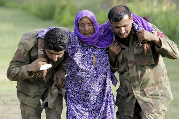 FILE - In this July 30, 2010, file photo, Pakistani army soldiers help an elderly villager evacuated from a flooded area in Nowshera, Pakistan. As Turkish forces invaded northern Syria in early October 2019, supporters of the offensive launched an online misinformation campaign. Dozens of misleading images claiming to show Turkey's soldiers cuddling babies, feeding hungry toddlers and carrying elderly women, including this image from 2010, spread across Twitter and Instagram where they were liked, retweeted and viewed thousands of times. (AP Photo/Mohammad Sajjad, File)
