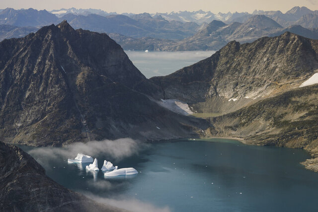 FILE - In this Aug. 14, 2019, file photo, icebergs are photographed from the window of an airplane carrying NASA scientists as they fly on a mission to track melting ice in eastern Greenland. The Trump administration is poised to announce an expanded diplomatic presence in Greenland and a new assistance package for the vast island aimed at thwarting growing Chinese and Russian influence in the Arctic. The announcement, expected Thursday, April 23, 2020, will come less than a year after President Donald Trump drew derision for expressing an interest in buying Greenland. (AP Photo/Mstyslav Chernov, File)