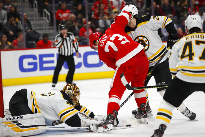 Boston Bruins goaltender Tuukka Rask, front left, stops a Detroit Red Wings left wing Adam Erne (73) shot in the second period of an NHL hockey game Sunday, Feb. 9, 2020, in Detroit. (AP Photo/Paul Sancya)