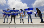 Anti-government protesters hold up flags and signs demanding the release of political prisoners on the sidelines of a Stations of the Cross procession on Good Friday in Managua, Nicaragua, Friday, April 19, 2019. Good Friday religious processions in Nicaragua's capital have taken a decidedly political tone as people have seized on a rare opportunity to renew protests against the government of President Daniel Ortega. (AP Photo/Alfredo Zuniga)
