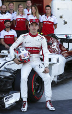 Sauber driver Charles Leclerc of Monaco poses with the team before the first free practice at the Yas Marina racetrack in Abu Dhabi, United Arab Emirates, Friday Nov. 23, 2018. The Emirates Formula One Grand Prix will take place on Sunday. (AP Photo/Kamran Jebreili)