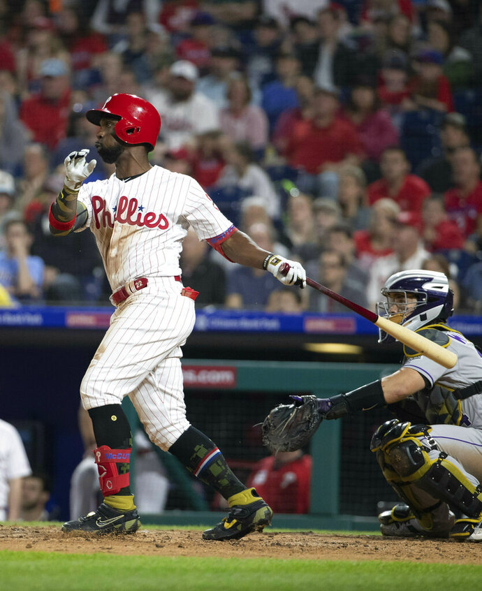 Philadelphia Phillies' Andrew McCutchen watches his two-run home run during the third inning of the team's baseball game against the Colorado Rockies, Friday, May 17, 2019, in Philadelphia. (AP Photo/Chris Szagola)