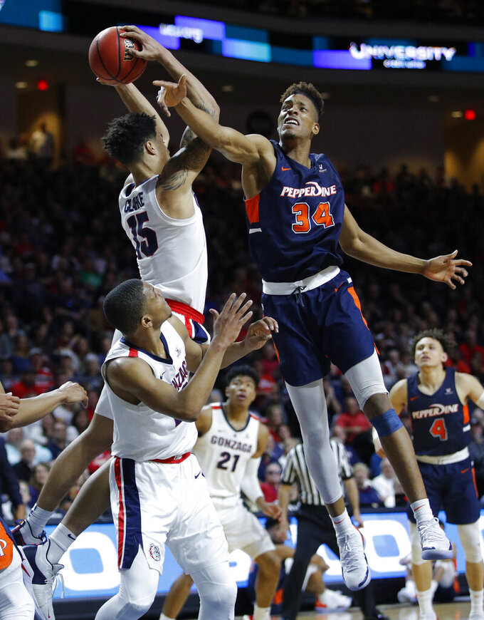 Pepperdine's Victor Ohia Obioha (34) and Gonzaga's Brandon Clarke (15) battle for a rebound during the second half of an NCAA semifinal college basketball game at the West Coast Conference tournament, Monday, March 11, 2019, in Las Vegas. (AP Photo/John Locher)