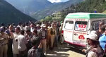 In this grab made from video provided by KK Productions, an ambulance waits to transport people injured in a bus accident in Kishtwar, about 217 kilometers (135 miles) southeast of Srinagar, Indian-controlled portion of Kashmir, Friday, Sept. 14, 2018. Police say a bus fell off a road into a deep gorge killing more than a dozen people and injuring an equal number. (KK Productions via AP)