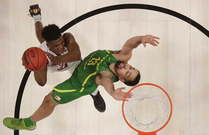 Wisconsin guard Khalil Iverson, left, shoots against Oregon forward Paul White during the first half of a first round men's college basketball game in the NCAA Tournament, Friday, March 22, 2019, in San Jose, Calif. (AP Photo/Ben Margot)