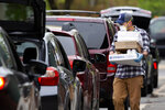 In this Friday, May 8, 2020 photo, Jack's Abby craft brewery employee Mike Oates carries an order to a customer in a line of cars waiting curbside in Framingham, Mass. Sales of wine, spirits and other alcoholic beverages have risen during the coronavirus pandemic. (AP Photo/Michael Dwyer)
