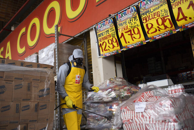 Members of the Red Cross disinfects a facility at the CEASA, Rio de Janeiro's main wholesale market, amid the new coronavirus pandemic in Rio de Janeiro, Brazil, Tuesday, June 23, 2020. (AP Photo/Silvia Izquierdo)