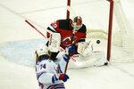 New York Rangers' Vitali Kravtsov, left, scores on New Jersey Devils goaltender Mackenzie Blackwood during the first period of the NHL hockey game in Newark, N.J., Sunday, April 18, 2021. (AP Photo/Seth Wenig)