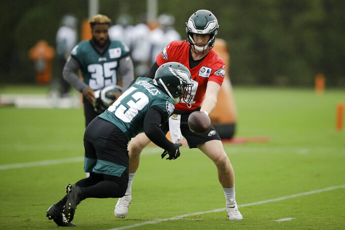 Philadelphia Eagles quarterback Carson Wentz (11) hands the ball off to running back Darren Sproles in action at the NFL football team's practice facility in Philadelphia, Thursday, Oct. 3, 2019. (AP Photo/Matt Rourke)