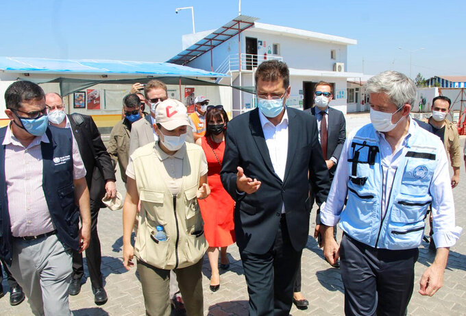 """Janez Lenarcic, EU commissioner for Crisis Management, second right, speaks with aid workers at the Bab- al-Hawa border crossing between Turkey and northern Syria, Thursday, July 8, 2021. A top EU official said Thursday that the closure of the only remaining border crossing that allows aid into areas held by Syrian insurgents would have """"catastrophic"""" consequences for millions of Syrians depending on assistance. Lenarcic, EU commissioner for Crisis Management, urged the U.N. Security Council to vote to keep the Bab- al-Hawa border crossing operational and for other border crossings to be reopened. (IHA via AP)"""