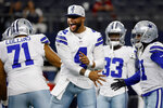 FILE - In this Saturday, Aug. 21, 2021, file photo, Dallas Cowboys' La'el Collins (71) and Dak Prescott (4) get ready for a preseason NFL football game against the Houston Texans in Arlington, Texas. On and off the field, NFL quarterbacks _ no surprise here _ are making the most money. Even in a year when the salary cap has decreased, the big name passers are getting richer. According to Forbes, the 10 biggest earners will collect about $418 million in salary, endorsements and other earnings.  That's an increase of 9% over 2020. Prescott tops the list mainly because of the four-year, $160 million contract he landed earlier in 2021.(AP Photo/Ron Jenkins, File)
