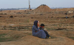 A protester and her child sit while inhaling teargas fired by Israeli troops near the fence of the Gaza Strip border with Israel during a protest east of Gaza City, Friday, Nov. 9, 2018. Gaza's Hamas rulers said Friday that deadly protests along Gaza-Israel perimeter fence have achieved some goals; $15 million from Qatar to help pay the salaries of civil servants. (AP Photo/Adel Hana)