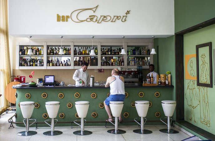 "FILE - In this Sept. 12, 2017, file photo, a customer sits at the lobby bar of the Hotel Capri in Havana, Cuba. Doctors are releasing the first detailed medical reports about the hearing, vision, balance and brain symptoms suffered in what the State Department has called ""health attacks"" on U.S. diplomats in Cuba. Still missing: A clear diagnosis of just what happened to trigger their mysterious health problems. (AP Photo/Desmond Boylan)"