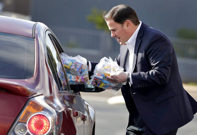 Arizona Gov. Doug Ducey, R, serves meals to school children Thursday, March 19, 2020, outside Sunset Elementary School in Phoenix. With all state schools shut down due to the COVID-19 coronavirus, many districts are continuing their distribution of breakfast and lunch curbside to kids 18 and under. (AP Photo/Matt York)