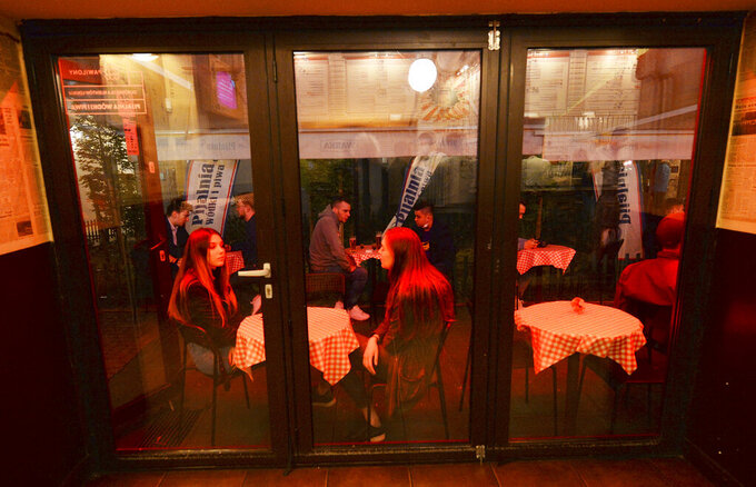 People gather and celebrate as bars, clubs and other establishments reopened in Poland after being closed for seven months, in Warsaw, Poland, Friday, May 14, 2021. (AP Photo/Czarek Sokolowski)