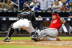 Miami Marlins catcher Bryan Holaday, left, tags out Washington Nationals' Asdrubal Cabrera at home plate during the fourth inning of a baseball game, Saturday, Sept. 21, 2019, in Miami. (AP Photo/Wilfredo Lee)