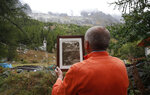 FILE - In this Thursday, Sept. 26, 2019 file photo, Marco Belfrond holds an old photo of the Plancipieux glacier, near Courmayeur, northern Italy, near the fast-moving melting glacier. A hotter world is getting closer to passing a temperature limit set by global leaders five years ago and may exceed it in the next decade or so, according to a new United Nations report released on Wednesday, Sept. 9, 2020. (AP Photo/Antonio Calanni)