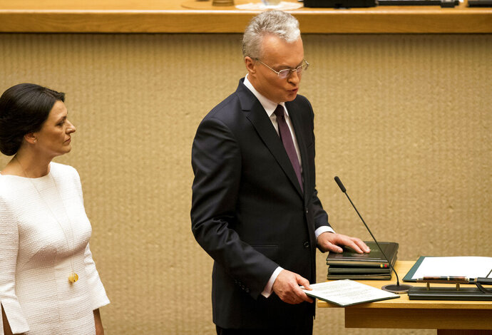 Lithuanian President-elect Gitanas Nauseda, flanked by his wife Diana Nausediene, takes the oath of office during his inauguration ceremony in the Lithuanian parliament in Vilnius, Lithuania, Friday, July 12, 2019.  Former bank analyst Nauseda has been sworn in as Lithuania's president taking the lead of the Baltic country of 3 million.(AP Photo/Mindaugas Kulbis)