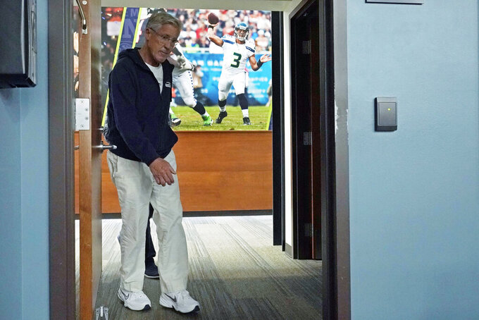 Seattle Seahawks head coach Pete Carroll walks past a photo of quarterback Russell Wilson in action as he arrives to talk to reporters before NFL football practice, Wednesday, Oct. 13, 2021, in Renton, Wash. Wilson is out with a finger injury and backup quarterback Geno Smith is scheduled to start Sunday on the road against the Pittsburgh Steelers in an NFL football game. (AP Photo/Ted S. Warren)