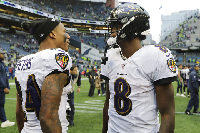 Baltimore Ravens quarterback Lamar Jackson (8) alks with cornerback Marcus Peters (24) after an NFL football game against the Seattle Seahawks, Sunday, Oct. 20, 2019, in Seattle. (AP Photo/John Froschauer)