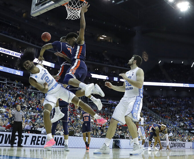 North Carolina's Coby White (2) loses control of the ball as Auburn's Horace Spencer, second from left, and Chuma Okeke defend and teammate Luke Maye (32) watches during the first half of a men's NCAA tournament college basketball Midwest Regional semifinal game Friday, March 29, 2019, in Kansas City, Mo. (AP Photo/Charlie Riedel)